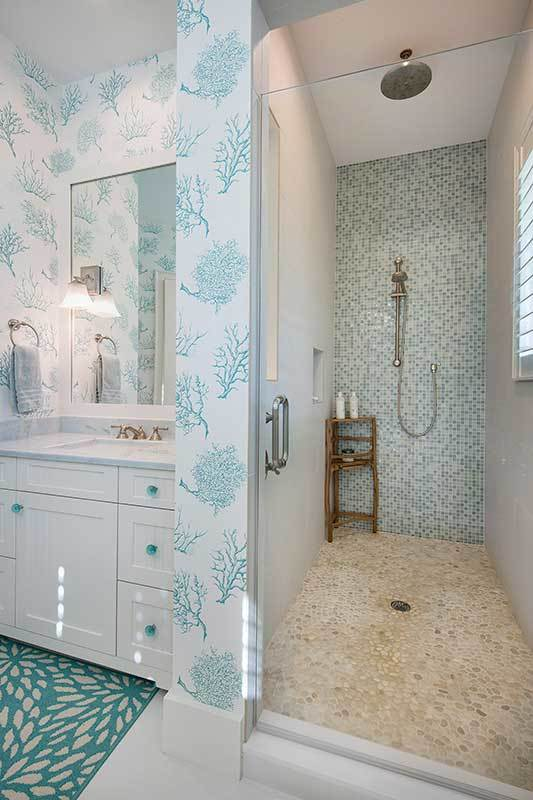 Walk-in shower with pebble flooring, mosaic tile accent wall, wooden rack, and chrome fixtures.