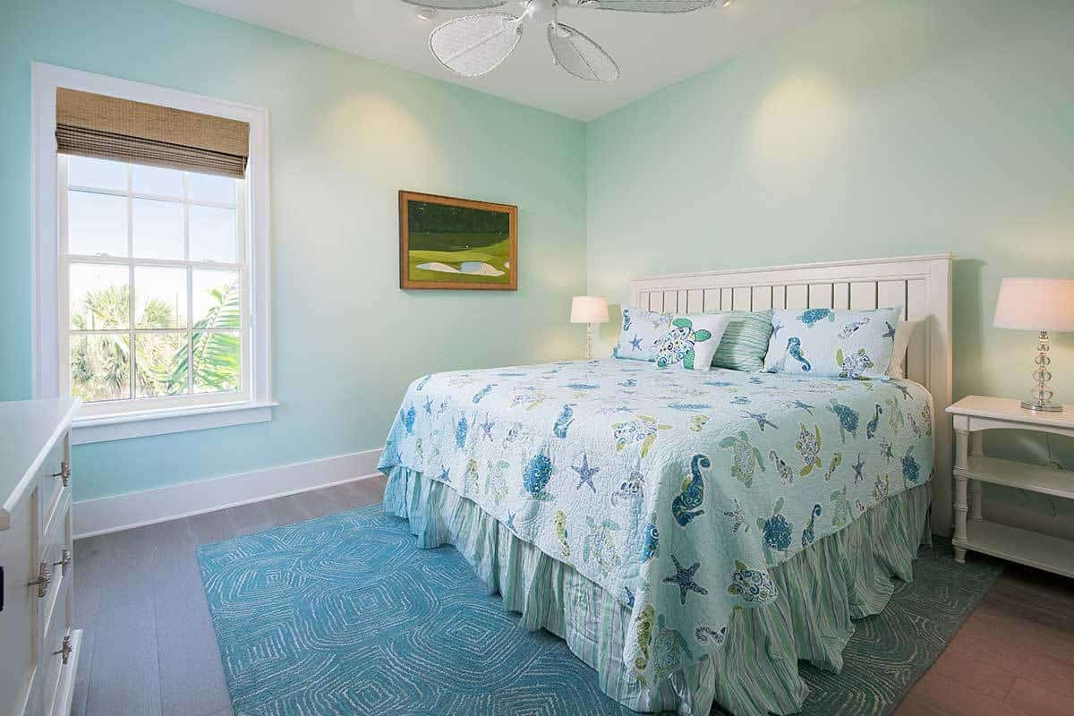 This bedroom offers white furnishings, a blue patterned rug, and a ceiling fan mounted on the regular ceiling.