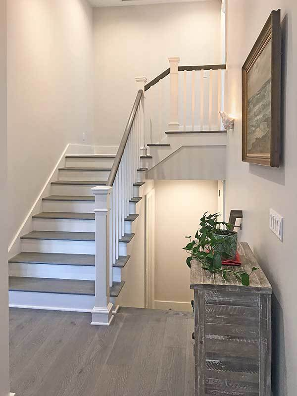 Wooden staircase leading down the garage. Its landing is filled with a rustic table and a framed artwork.
