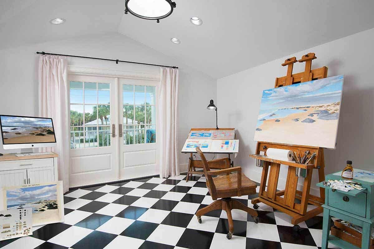 Studio with art tools, checkered flooring, and a french door that leads out to the covered balcony.