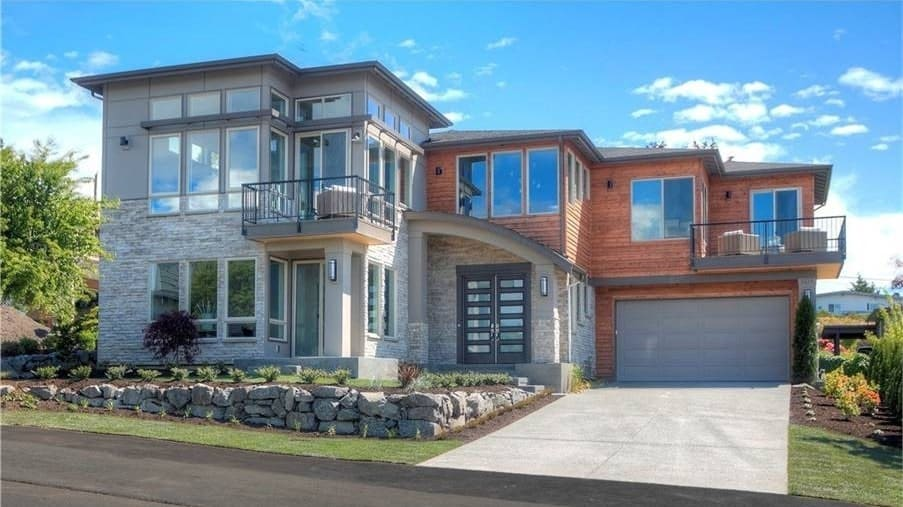 Front exterior view with wood and stone cladding, upper decks, and a striking entry with a french front door.
