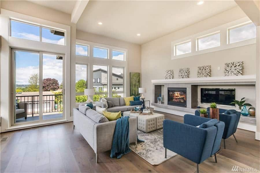 The living room has gray sofas, blue armchairs, a modern fireplace, and a wall-mounted TV.