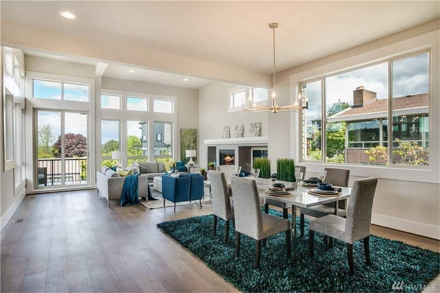 A farther view shows the dining area with a contemporary chandelier, gray upholstered chairs, and a rectangular dining table sitting on a shaggy area rug.