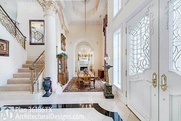 Foyer with white ornate door and a great view of the formal dining room with a display cabinet and wooden dining set on a classic area rug.
