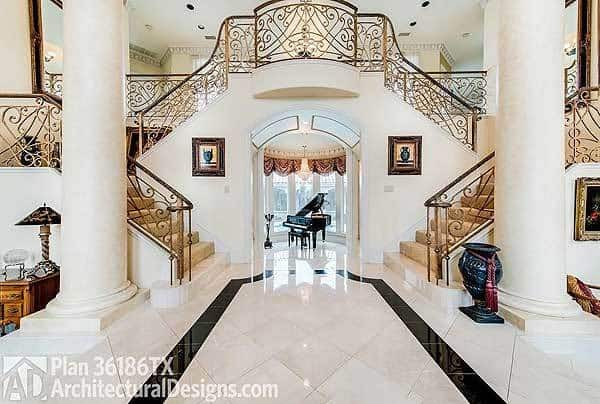 Double staircase and columns along with an open archway that leads to the music room.