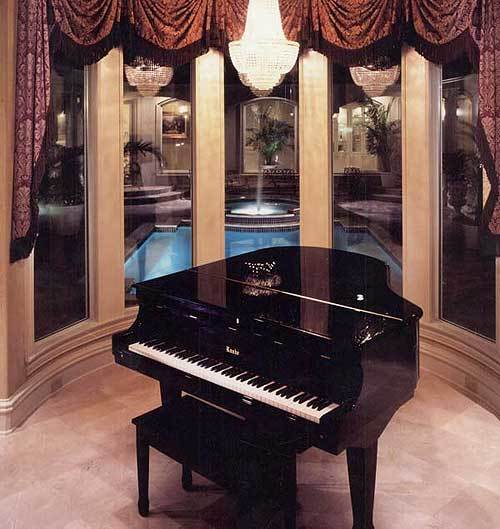 Music room with a grand piano, beaded chandelier, and a bay window overlooking the courtyard pool.