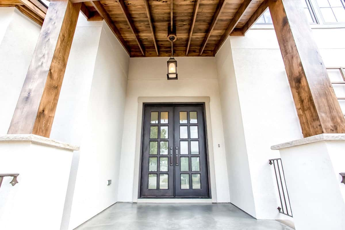 Covered entry with a french front door, tapered columns, and a beamed ceiling with a hanging lantern pendant.