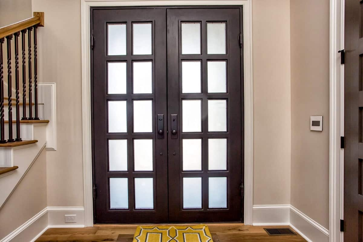 The french front door opens to the foyer with beige walls and hardwood flooring topped by a yellow patterned rug.