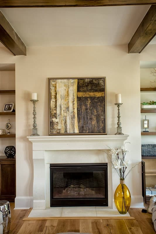 A large glass vase, candle holders, and a framed painting complement the glass-enclosed fireplace.