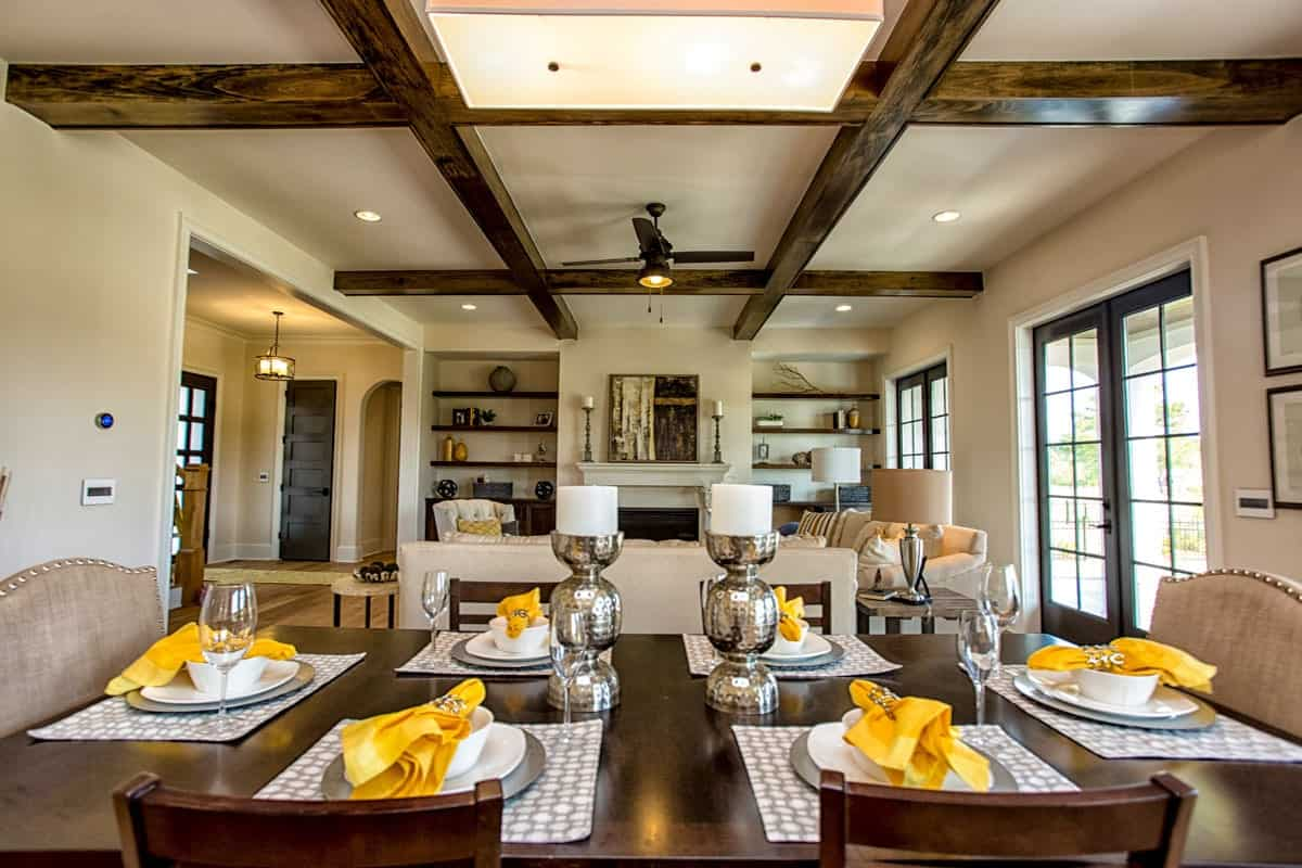 View of the living room from the dining area showcasing its wooden coffered ceiling.