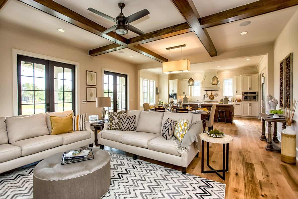 The living area has beige sectionals, round tables, and a tufted ottoman that sits on a chevron area rug.