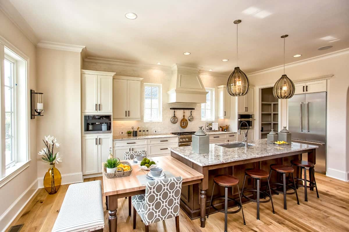 Eat-in kitchen with white cabinetry, stainless steel appliances, granite countertops, and a breakfast island attached with an eating counter.