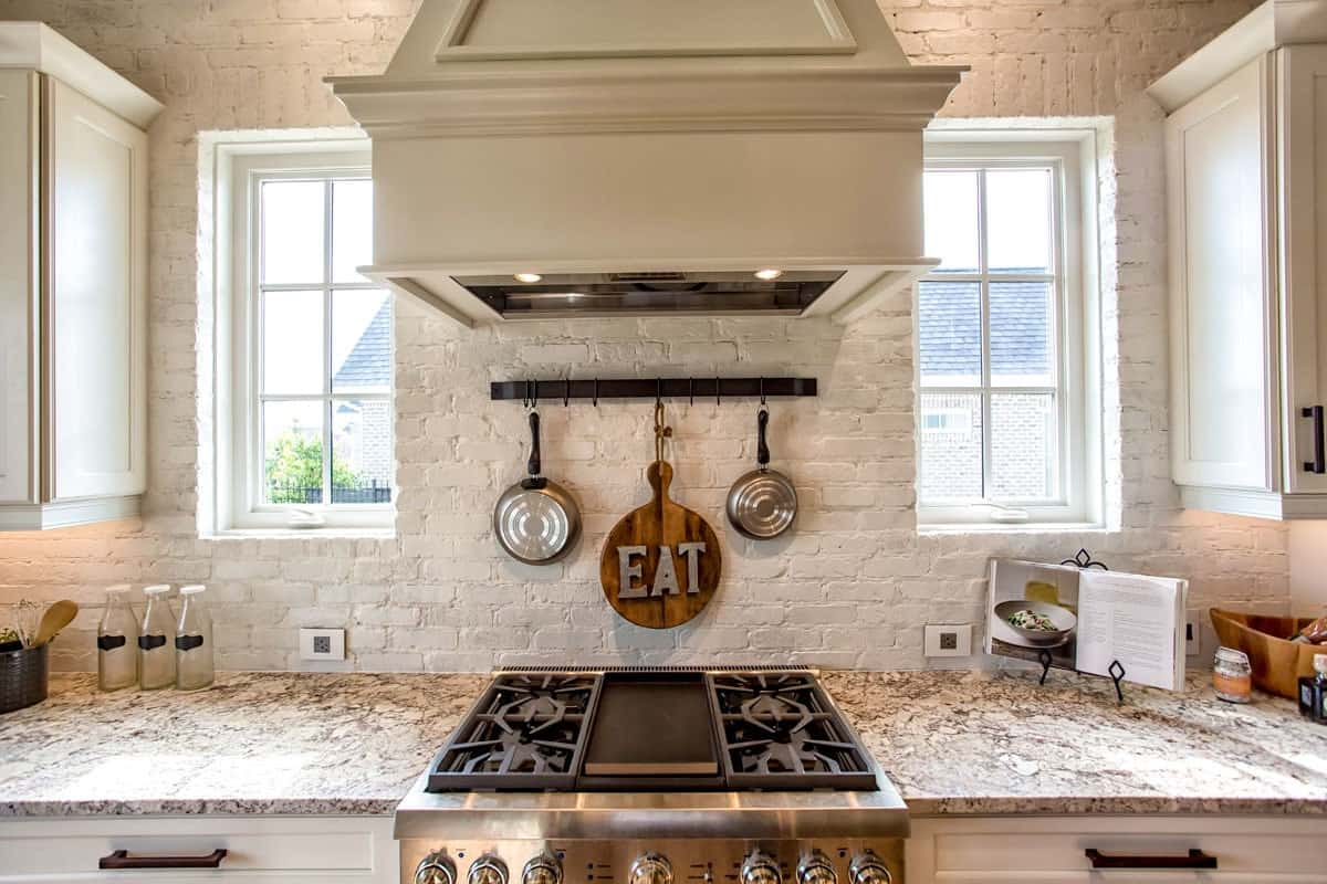 White framed windows flank the bespoke hood that's fixed above the cooktop.