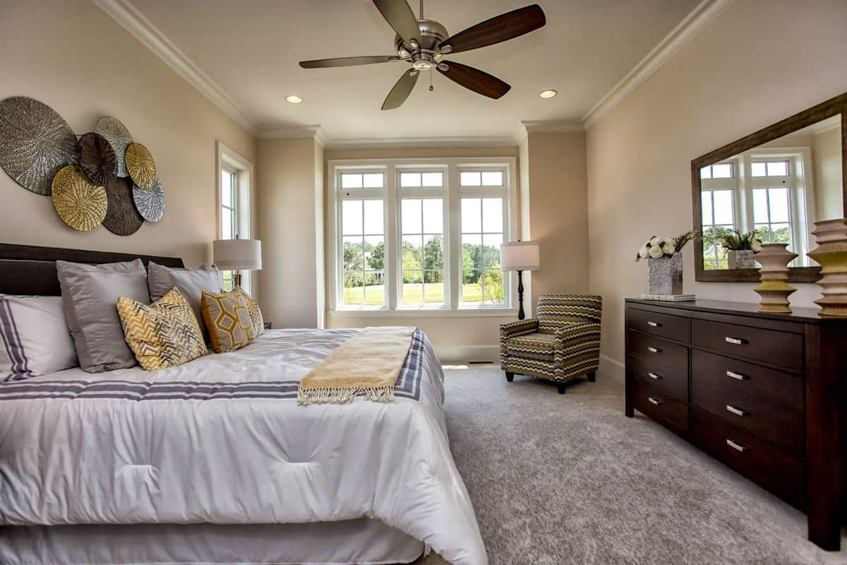 The primary bedroom has a striped armchair, a dark wood dresser, and a cozy bed adorned by round wall arts.