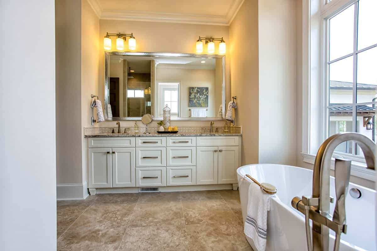 Primary bathroom with dual sink vanity and a freestanding tub placed under the white framed window.