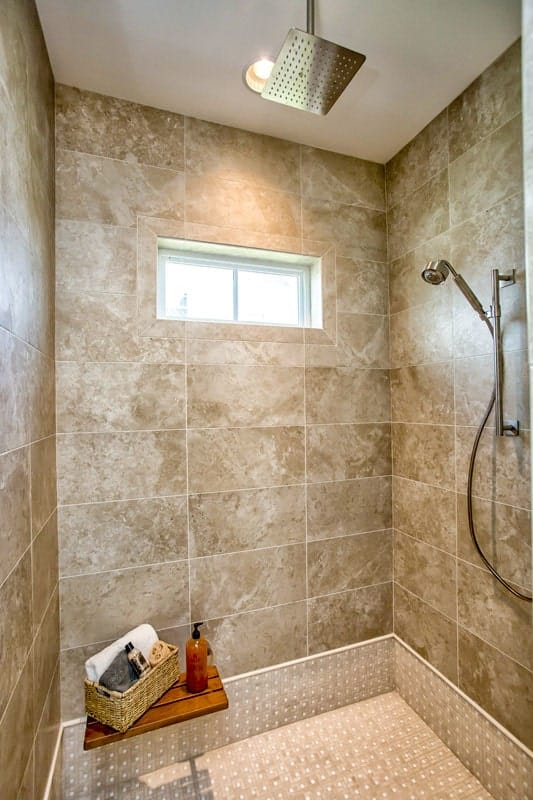 The walk-in shower has tiled walls, a wooden shelf, and chrome fixtures.