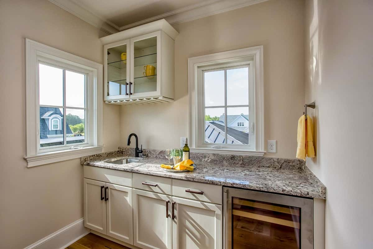 Wet bar with granite countertop, white cabinets, and a wine fridge.