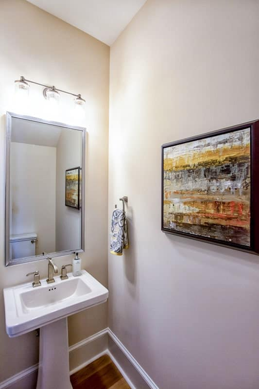 The powder room has a sink pedestal, a large mirror, glass sconces, and a bold artwork.