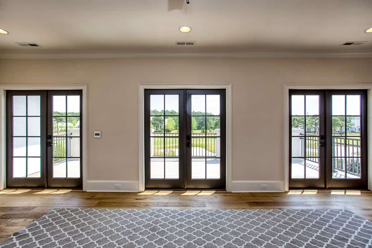 Recreation room with a huge patterned rug and three french doors that lead out to the spacious balcony.