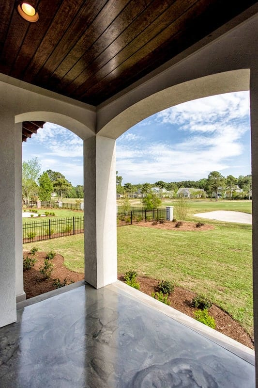 Covered patio with open archways and wood-paneled ceiling fitted with recessed lights.