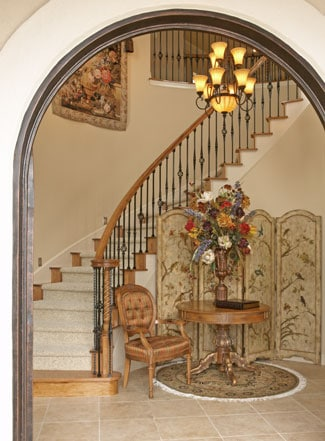 The arched front door opens to the foyer with a tufted armchair, a round table, and a carpeted staircase well-lit by warm glass chandelier.
