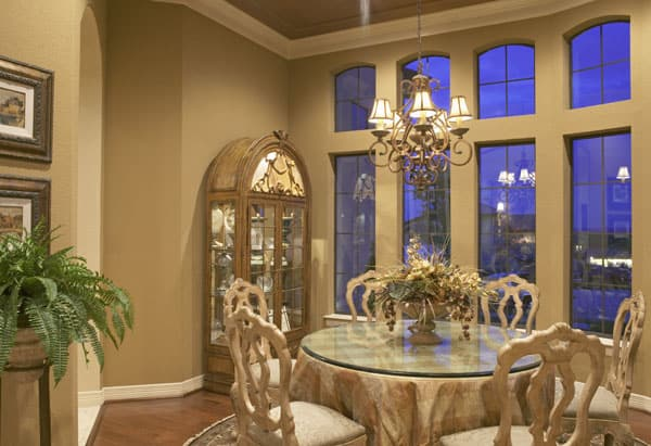 Dining room with an arched display cabinet, an ornate chandelier, glass top dining table, and cushioned wooden chairs.
