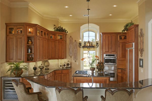 The kitchen has natural wood cabinetry, a curved peninsula, and a wrought iron chandelier hanging over the cooktop island.