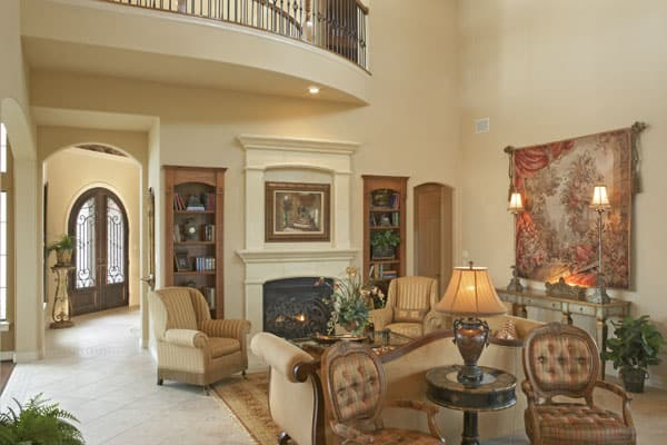 Living room with classy beige seats, wooden tables, a marble fireplace, and a tapestry adorning the beige wall.