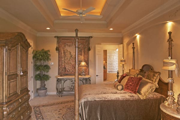 The primary bedroom has a tray ceiling, four-poster bed, wooden wardrobe, and an ornate console table.