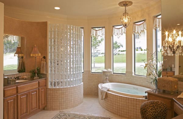 The primary bathroom is equipped with a deep soaking tub, wooden vanities, and a walk-in shower enclosed in a glass block wall.