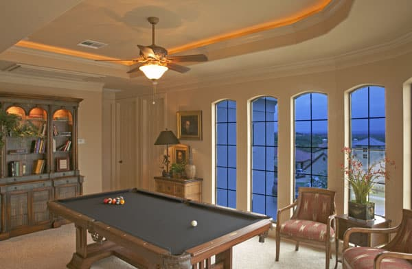 Game room with wooden cabinets, patterned armchairs, and a black billiard table.