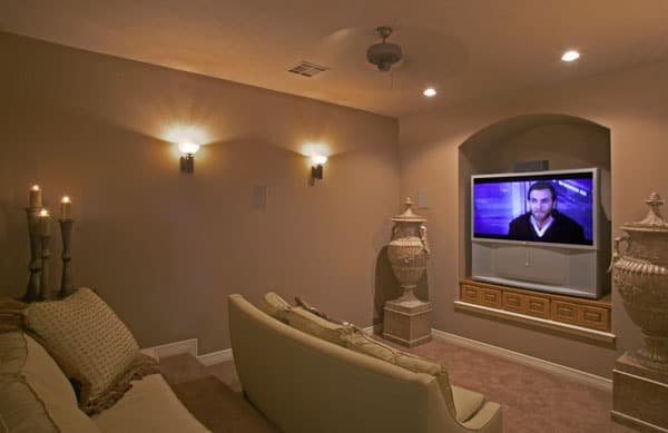 Media room with beige seats, vase pedestals, glass sconces, and a TV fitted on the arched inset niche.
