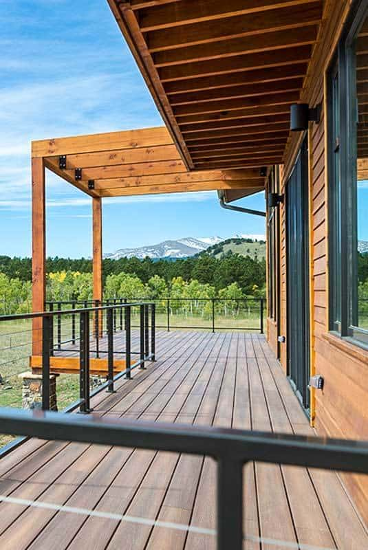 The deck features a wide plank flooring and wrought iron railings.
