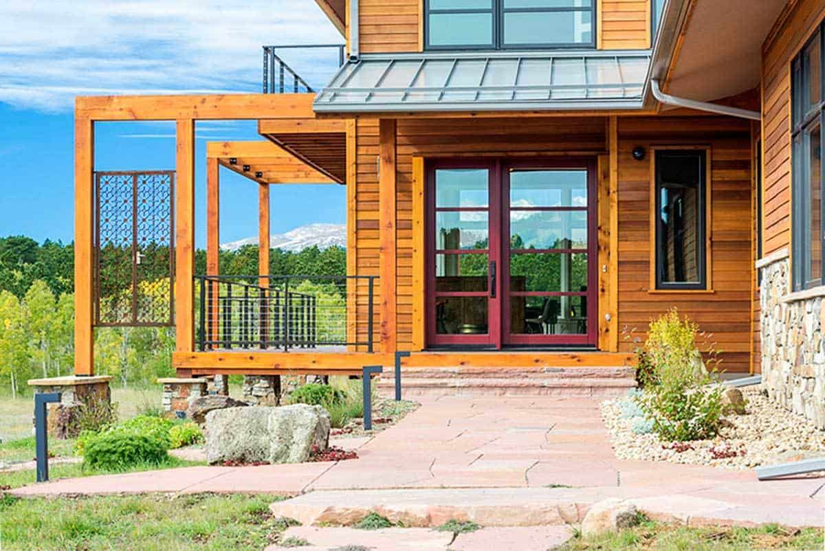 Home entry with a red-framed glass door that stands out against the wooden exterior walls.