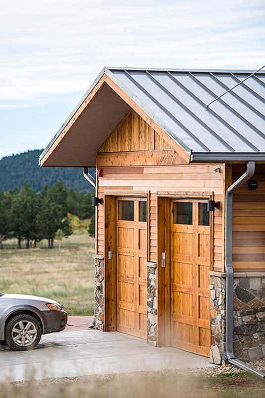 The double garage has a gable roof, stone accents, and wooden doors that blend in with the walls.