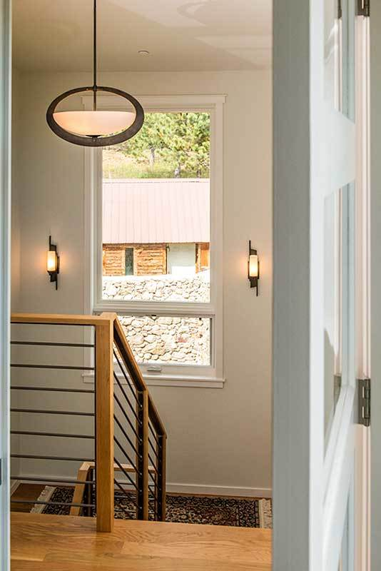 Staircase landing with cylindrical sconces and a picture window overlooking the courtyard.