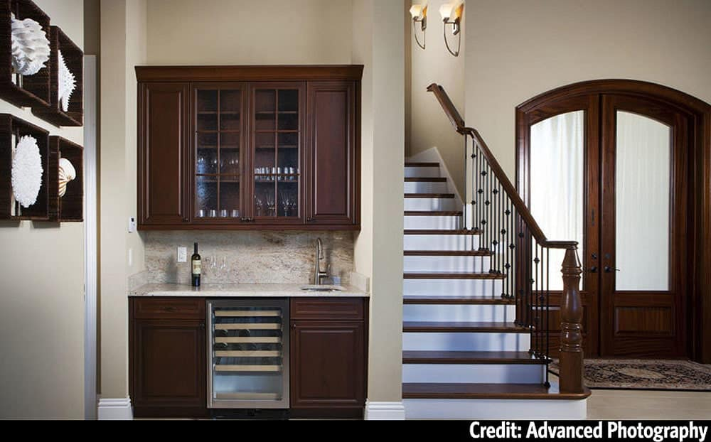 Foyer with an arched french entry door, a traditional staircase, and a wet bar.