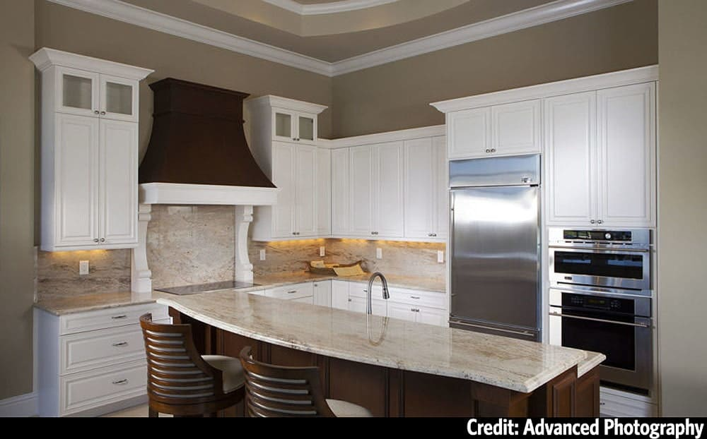 The kitchen is equipped with stainless steel appliances, granite countertops, white cabinetry, and a two-tier island.