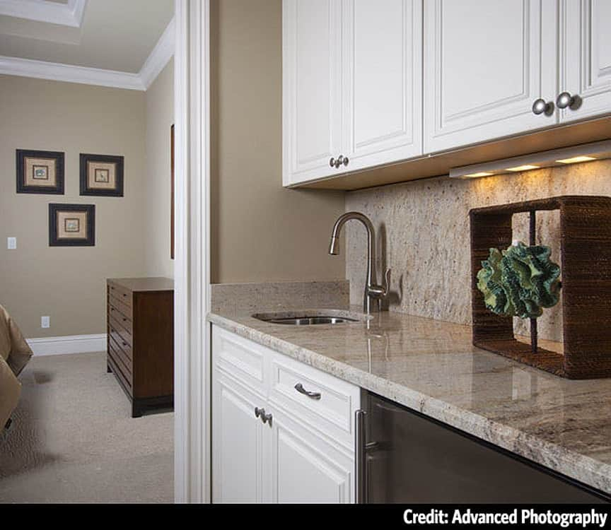A closer look at the wet bar with white cabinets, granite countertops, and an undermount sink.