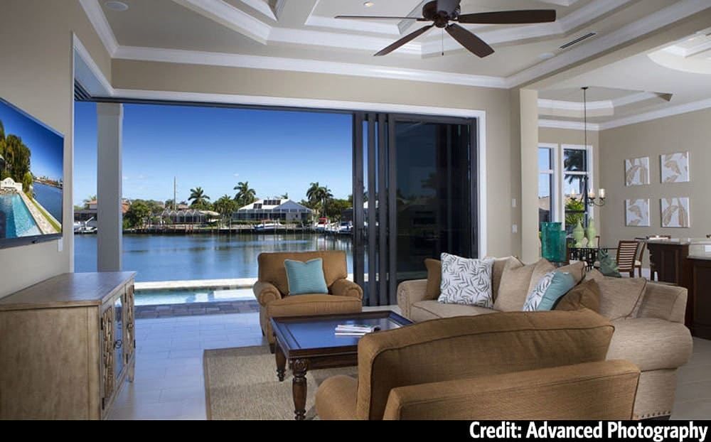 The living room has a beige sofa, brown armchairs, wooden tables, and sliding glass doors that open to the rear patio.