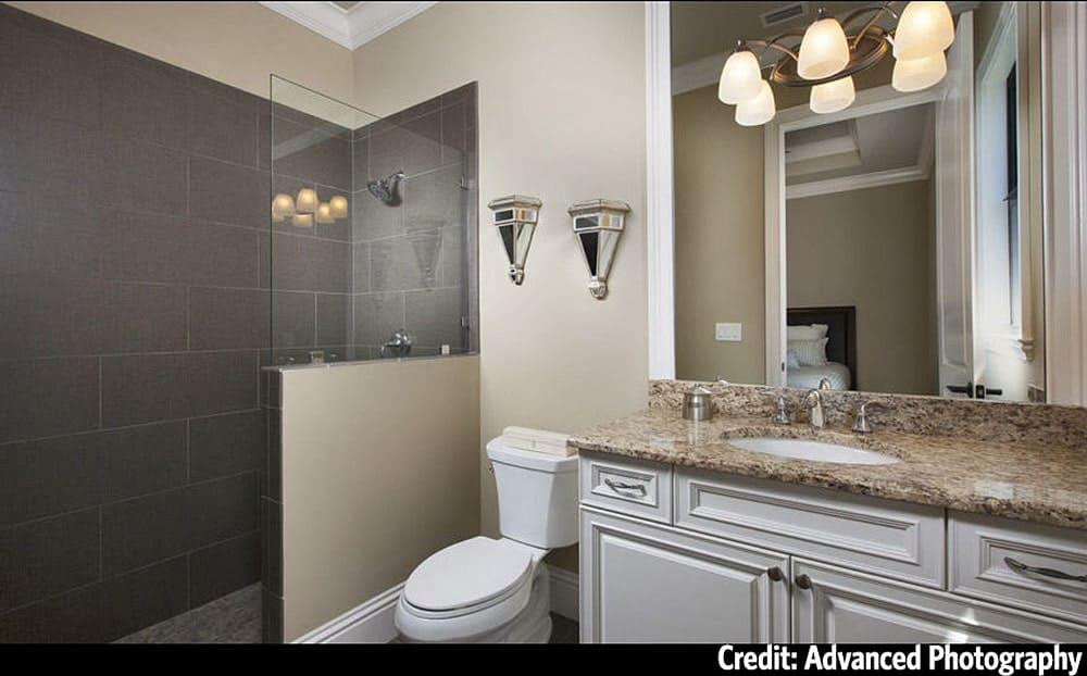 This bathroom offers a granite top vanity, a toilet, and a walk-in shower.