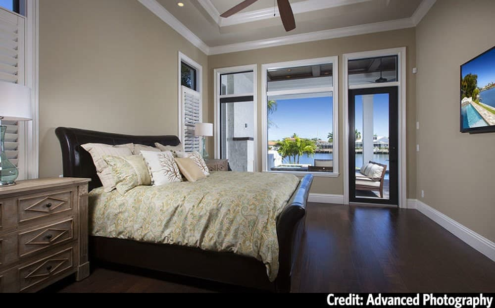 Primary bedroom with wooden furnishings, tray ceiling, dark hardwood flooring, and private access to the covered lanai.