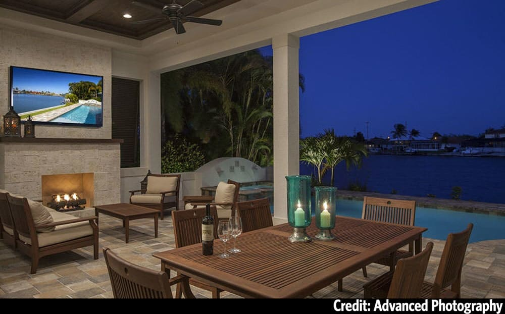 Covered lanai with wooden dining set, cushioned seats, and a fireplace with a wall-mounted TV on top.