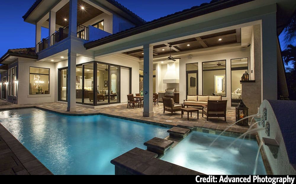 Rear exterior view showing the covered lanai along with a stunning pool that's integrated with a spa.