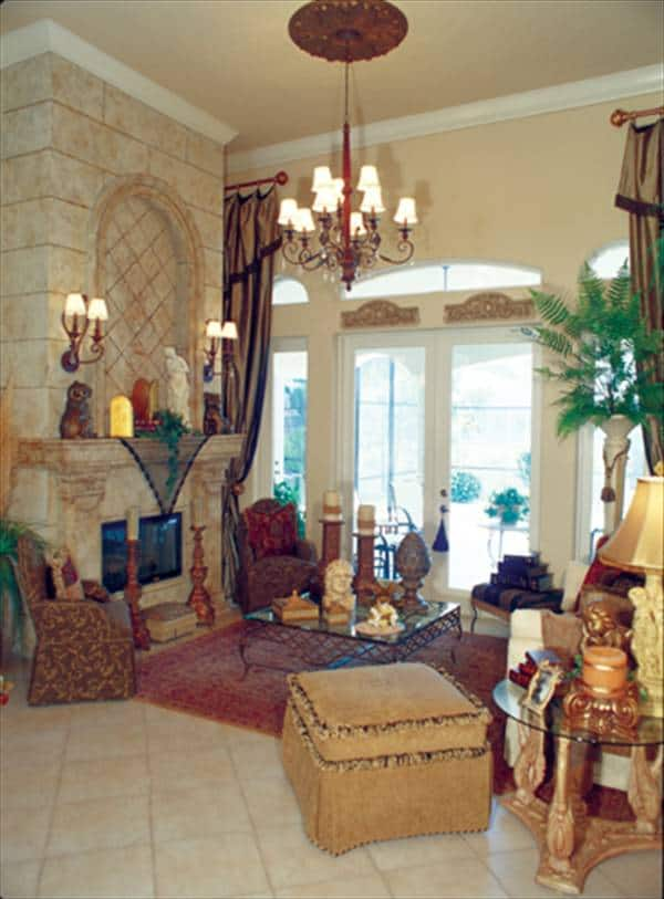 The living room has classy patterned seats, a glass top coffee table, a marble fireplace, and an ornate chandelier.