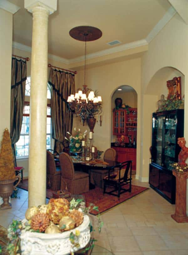 Dining room with an arched window, oval dining set, and a black display cabinet placed against the arched inset wall.