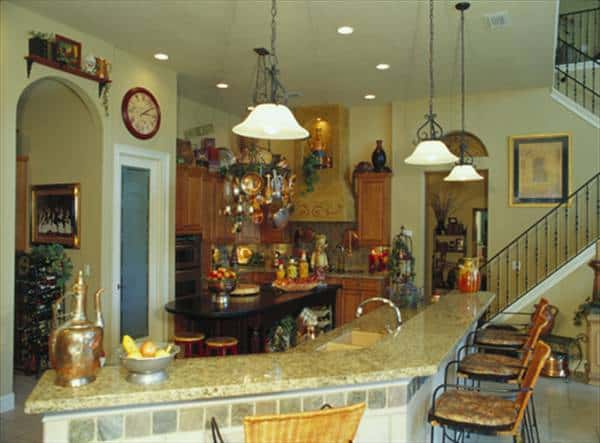 The kitchen is equipped with a two-tier island bar, wooden cabinetry, granite countertops, and glass dome pendants.