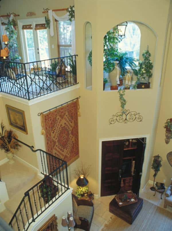 View of the family room from the balcony loft showing the entertainment center enclosed in a wooden double door.