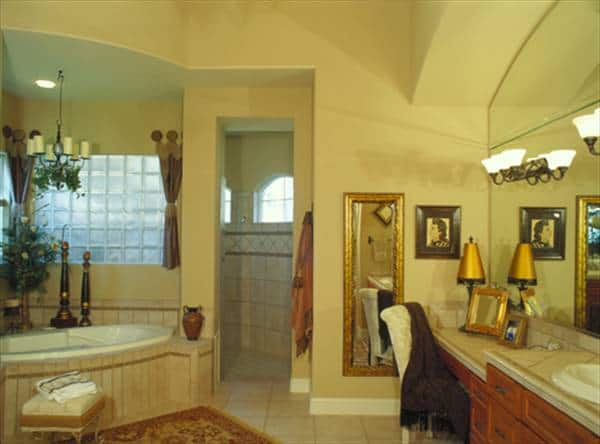 The primary bathroom has a walk-in shower, dual sink vanity, and a corner tub fixed under the glass block window.