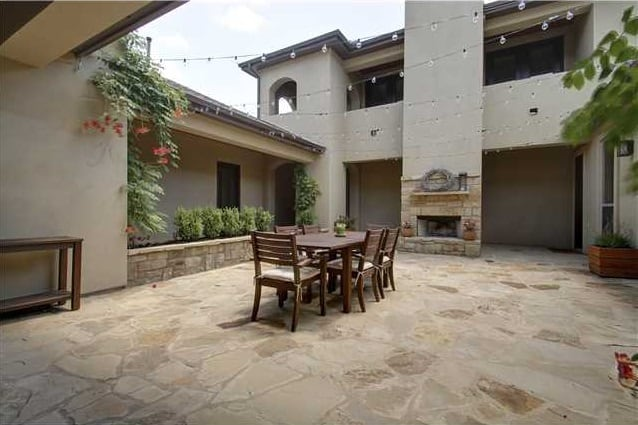 Courtyard with a wooden dining set and a fireplace that blends in with the flagstone flooring.